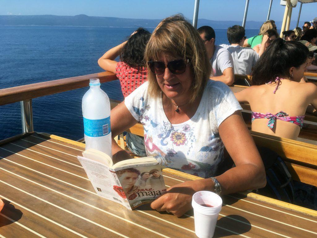 Bente fra Oslo leser seg bort. Akkurat her leser hun seg bort i Bare Maja på båten mellom Podgora og Hvar i Kroatia.