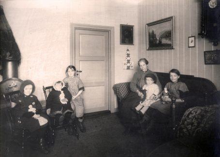 Mor med fem barn fotografert i stuen i leilighet i Stavangergaten. Foto: Ukjent fotograf / Norsk Teknisk Museum