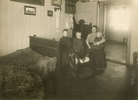 Mor med tre barn fotografert i oppholdsrom i leilighet i Stavangergaten. Foto: Ukjent fotograf / Norsk Teknisk Museum
