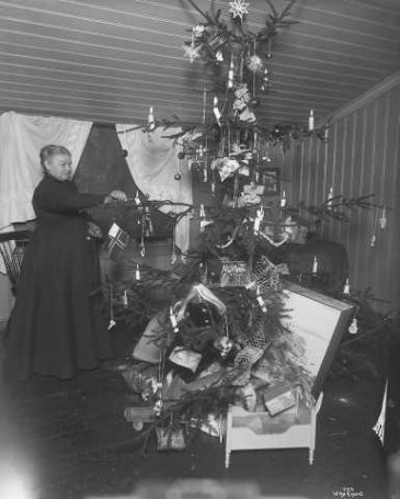 Mor i huset tenner julelysene. 1902, A.B. Wilse (foto).